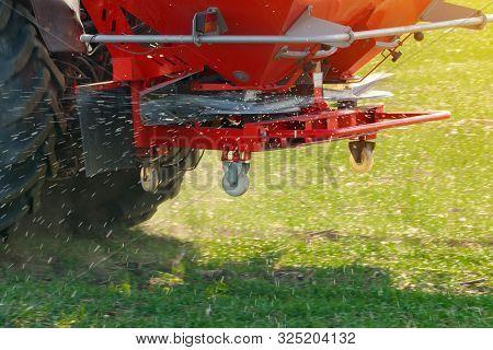 Unrecognizable Farmer In Agricultural Tractor Is Fertilizing Wheat Crop Field With Npk Fertilizer Nu