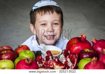 Cute Adorable Smiling Jewish Caucasian Boy With A Kippah On His Head Sitting By A Plate Of Split Pom