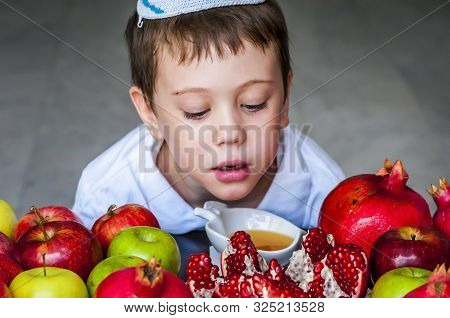 Cute Adorable Jewish Caucasian Boy With A Kippah On His Head Sitting By A Plate Of Split Pomegranate