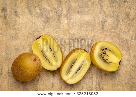 row of cut gold kiwifruit berries against  textured bark paper with a copy space