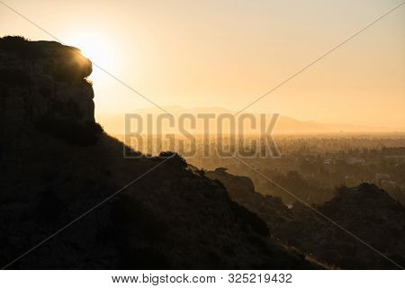 Hazy San Fernando Valley dawn view from the Santa Susana Mountains in the city of Los Angeles, California.  The San Gabriel Mountains are in the background.