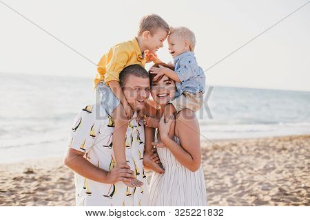Happy Family Having Fun With Their Little Children On Beach At Sunset