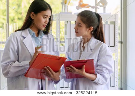 Two Chemical Young Woman Holding Document In Their Hands While Talking About Examination Biotechnolo