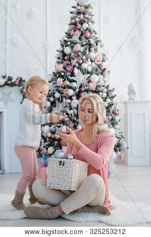Merry Christmas And Happy Holidays. Mom And Daughter Decorate The Christmas Pink Tree Indoors. New Y