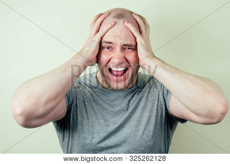 A Portrait Of A Bald Man Is Sad Against A Gray Background. Problem Of Male Pattern Baldness. Sadness