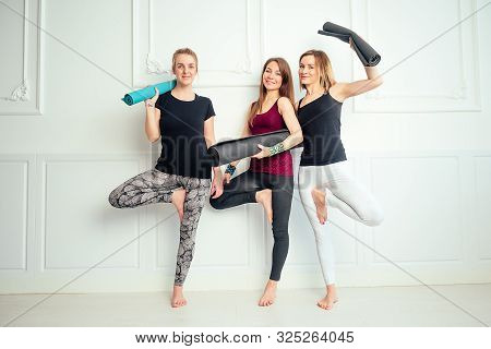 Happy Group Of People Three Women Practicing Yoga In Fun In The Studio. Groups Of Meditation And Sup