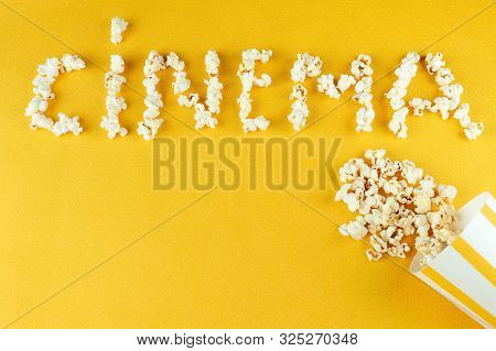 Popcorn Scattered From A Paper Striped On A Yellow Background Inscription Cinema. The Concept Of Hom
