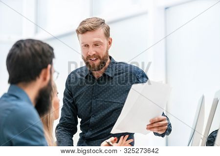 Businessman With Documents Explaining Something To His Colleagues