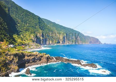 Stunning Cliffs On The Northern Coast Of Madeira Island, Portugal. Steep Green Rocks, Small City And