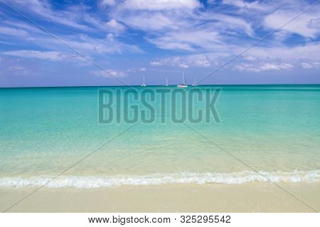 Tropical Beach With Soft Wave On Blue Sea And Sky. Background