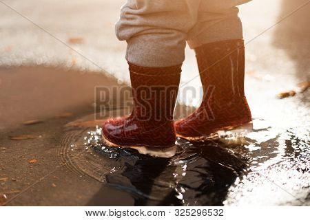 Little Girl In Red Rainboots Playing In Puddle After Rain. Happy Fall Childhood Activity