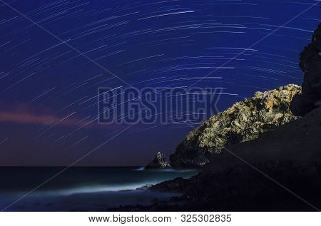 Star Trails Over A Rocky Headland In Tenerife On The South Coast, With The Sea Hitting A Volcanic Be