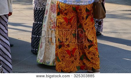 Various motifs of batik sarongs, which are being hit by a group of men and women poster