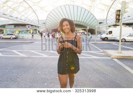 Carefree Woman Chatting Online While Walking Across Street. Young Black Woman Going Outside, Using M