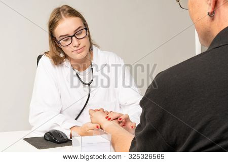A Doctor Manually Measures The Pulse On A Patient's Wrist