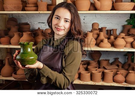 A Young And Cheerful Woman Holding A Vase Of Clay. The Potter Works In A Pottery Workshop With Clay.