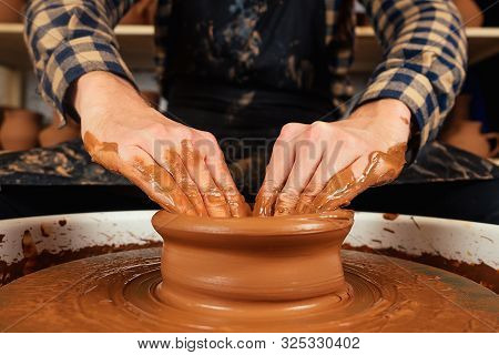 The Hands Of A Man In Clay On A Potters Wheel Mold A Vase. The Potter Works In A Pottery Workshop Wi