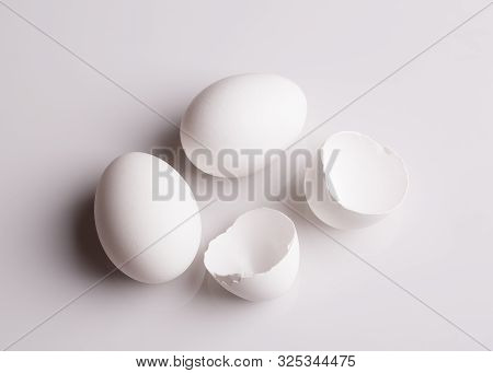 Two Whole Chicken Eggs And One Broken. An Empty Broken Egg. Conceptual Shot. Chicken White Eggs. Chi
