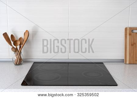 Black Ceramic Induction Stove With Wooden Flatware. Modern Apartment With Contemporary Interior, Bui