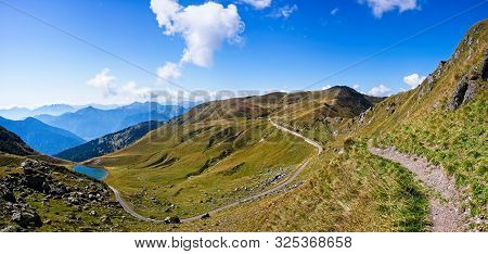 Mountain Panorama With Alpine Lake,  Blue Sky And Clouds. Alps Italy. Friuli.