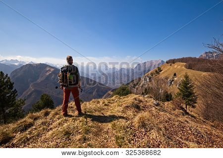 Hiker With Backpack Standing On Top Of A Mountain And Watching The Landscape.