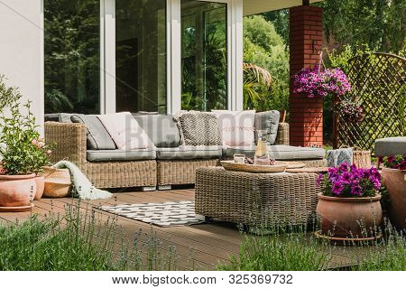 Classy Furniture On Wooden Terrace In Green Beautiful Garden