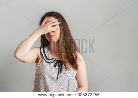 Emotions And People. A Young Brunette In A Blouse Covered Her Eyes With Her Hand And Peeps Through I
