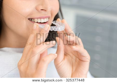Dental Treatment Concept. Cropped Image Of Young Woman Holding Invisible Braces, Whitening Tray, Fre
