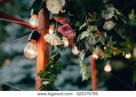 Decoration Wedding Arch With White And Pink Flowers On A Green Natural Background. Decorative Garlan