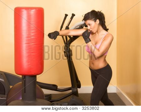 Attractive woman kickboxing using red punching bag poster