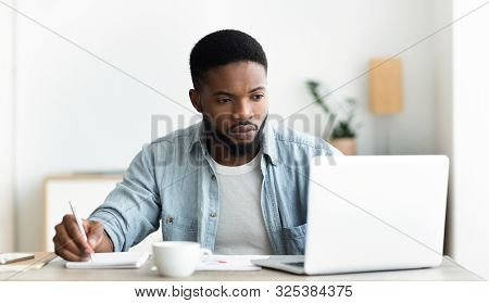 Job Search. Unemployed Man Using Laptop Searching For Vacancies Online In Internet And Taking Notes,