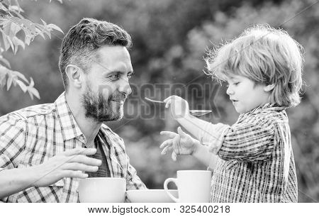 Feed Son Solids. Dad And Boy Eat And Feed Each Other Outdoors. Ways To Develop Healthy Eating Habits