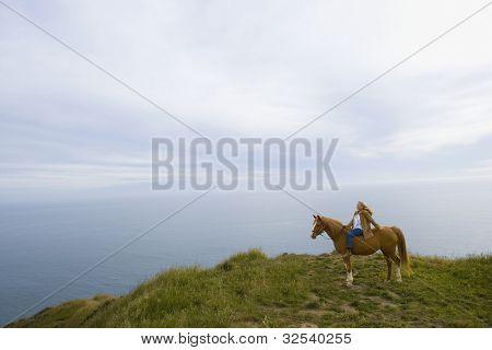 Senior woman horse riding bareback on cliff