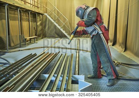 Sandblasting in chamber. Worker makes sand blast cleaning of metal detail