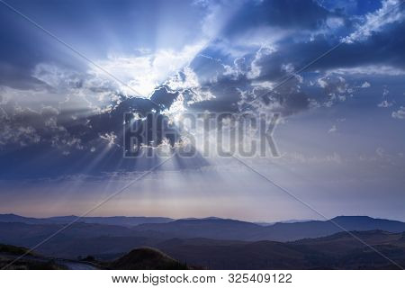 Sun Beams Breaking Through Clouds. Blue Sky Over Hill And Mountains. Dramatic Sky. Beautiful Concept