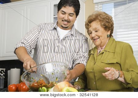 Hispanic mother and adult son preparing food in kitchen