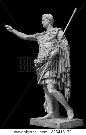 Caesar Augustus, the first emperor of Ancient Rome. Bronze monumental statue in the center of Rome isolated on black background by clipping path