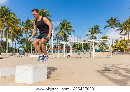 Jump box training man atlhete jumping doing strength workout outside in beach calisthenics park in South Beach, Miami, Florida.