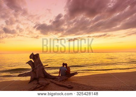 Couple on beach at sunset silhouettes - summer travel holidays in Caribbean destination. Romantic beach couple honeymoon Lovers enjoying watching sunset sitting on tree trunk by the ocean.