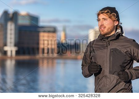 Winter running athlete man jogging outdoor in city outside wearing cold weather accessories - hat ,gloves , windproof sport jacket. Active healthy lifestyle.