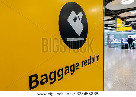 BAGGAGE RECLAIM SIGN, HEATHROW AIRPORT, FEBRUARY 21 2019, Baggage reclaim sign and passenger with rolling suitcase at Heathrow Airport Terminal 5, London, England, Great Britain, Europe