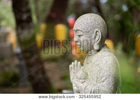 stone statue of Earth Store Bodhisattva in a garden