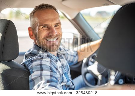 Attractive Man Driving A Car On A Clear Day. Buying Or Renting A Car.