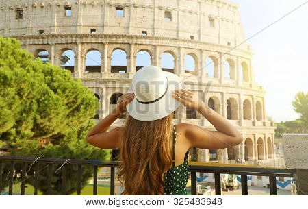 Travel In Italy. Back View Of Beautiful Girl Visiting Colosseum Landmark At Sunset In Rome. Summer H