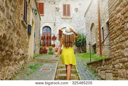 Beautiful Curious Young Woman With Yellow Dress And Hat Goes Upstairs In Street In Assisi, Italy. Re