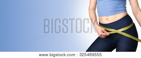 Woman Measuring Her Body. Slim Woman Measuring Her Hips And Buttocks Isolated On Blue Background. He
