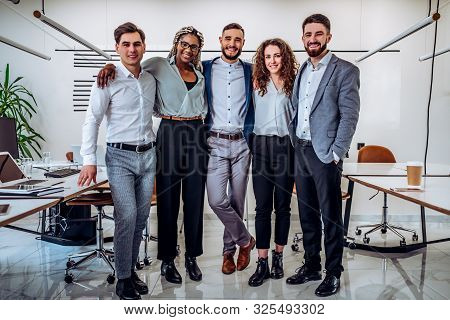 Full Lenght Shot Group Of Young Successful Multiethnic Business People Standing In Office Looking At