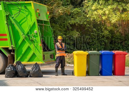 Garbage Removal Worker In Protective Clothing Working For A Public Utility Emptying Trash Container.