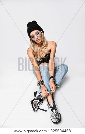 Young Grunge Style Woman In Torn Jeans, Leather Bralet, Knitted Winter Hat And Glasses Is Sitting On