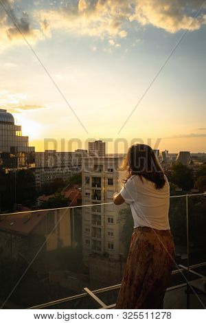 Woman In Sunset. Lifestyle Concept. Hipster Woman On Balcony In Sunset In City. City Lifestyle. Peop